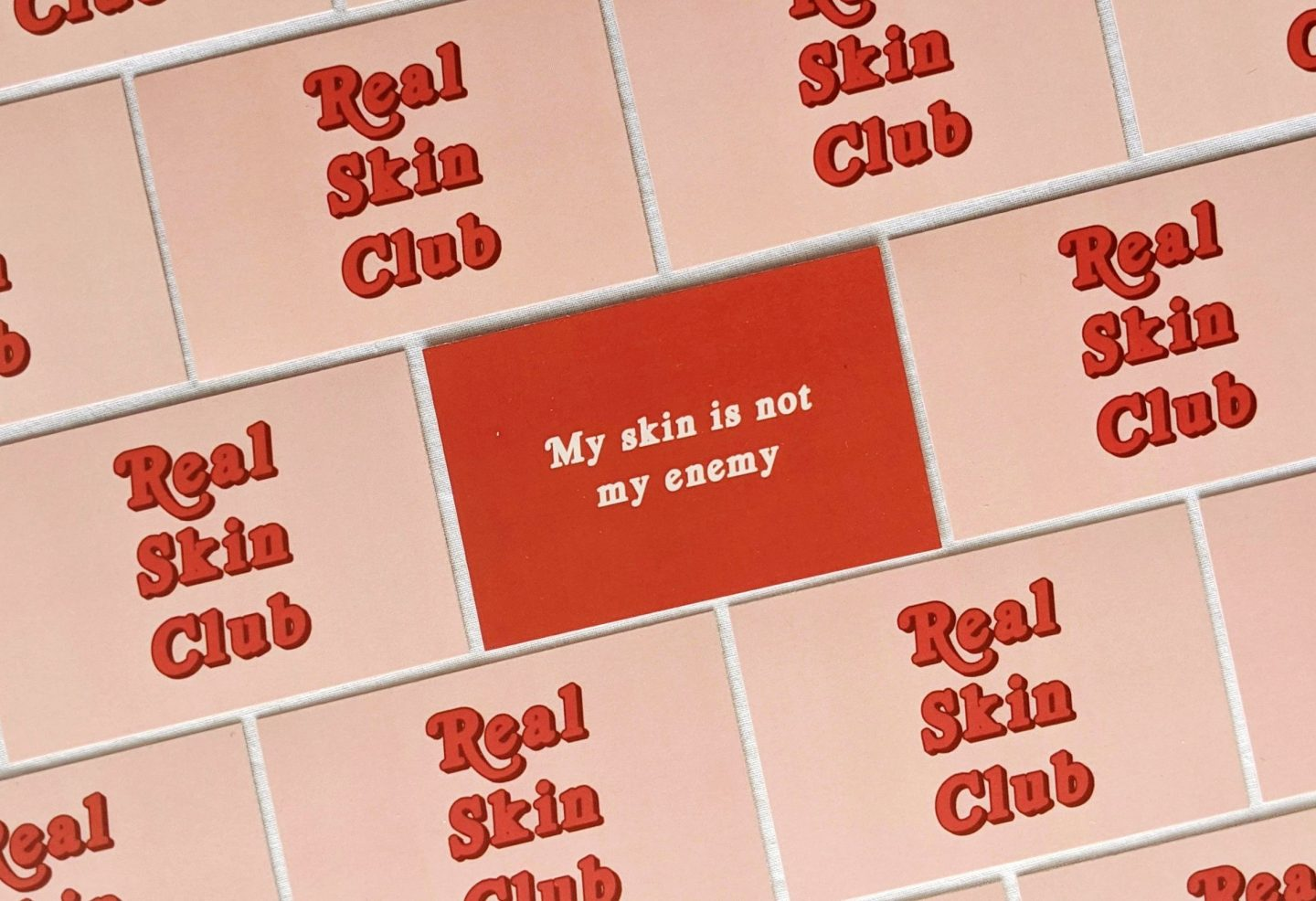 Photo of a Real Skin Club Affirmation Card, which reads 'My skin is not my enemy'. This is surrounded by cards featuring the Real Skin Club logo.  Positive affirmations for skin positivity.